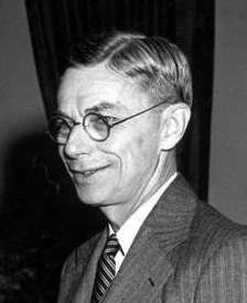Head and shoulders of smiling man in suit and tie with round dark-rimmed glasses. This is a detail from the picture below.