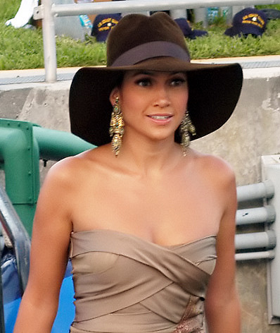 A middle aged woman, wearing a brown hat  and tan dress