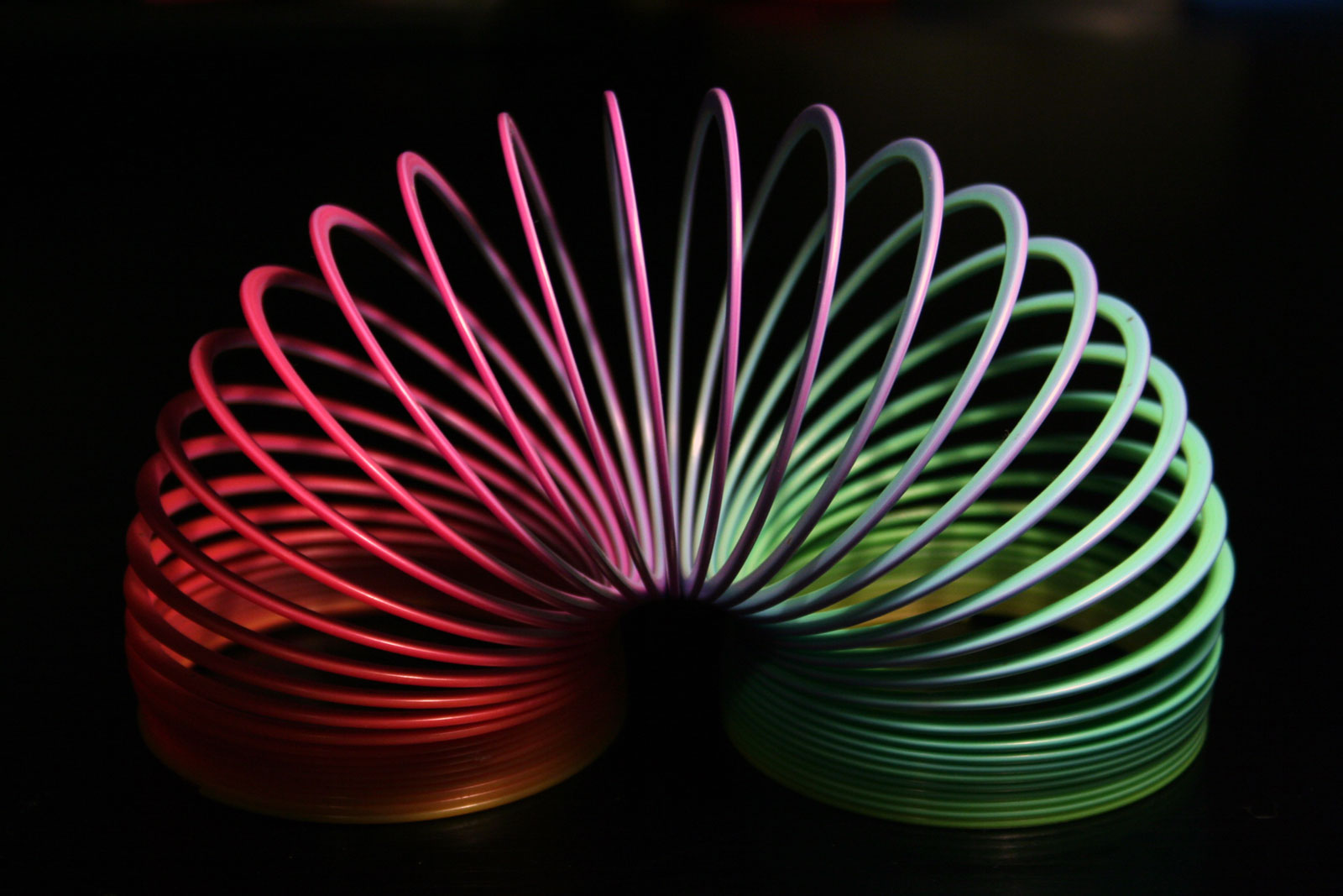 rainbow plastic slinky in arc shape