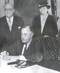 Francis Perkins looks on as Roosevelt signs the National Labor Relations Act