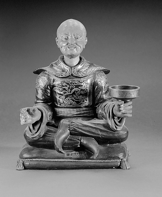 Mandarin sitting on cushions, holding a round dish in his left hand