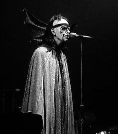 "Gabriel in 1974 performing ""Watcher of the Skies"", dressed in a cape with bat wings and fluorescent makeup."