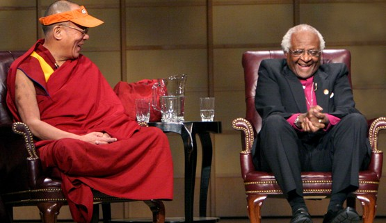 two people sitting on a stage, Desmond Tutu and Dalai Lama