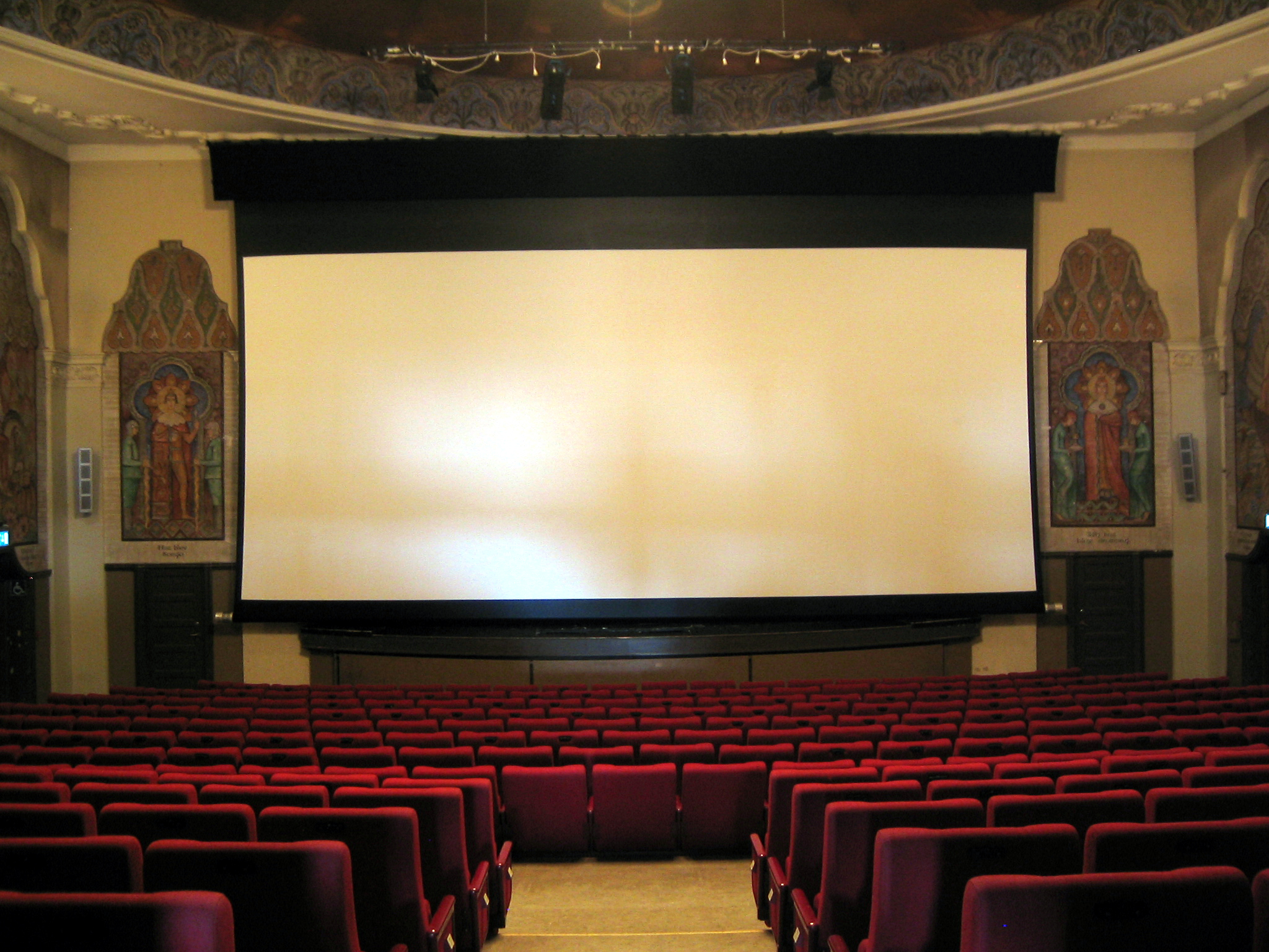 Film audiences are typically seated in comfortable chairs arranged in close rows before a projection screen. Norway (2005)