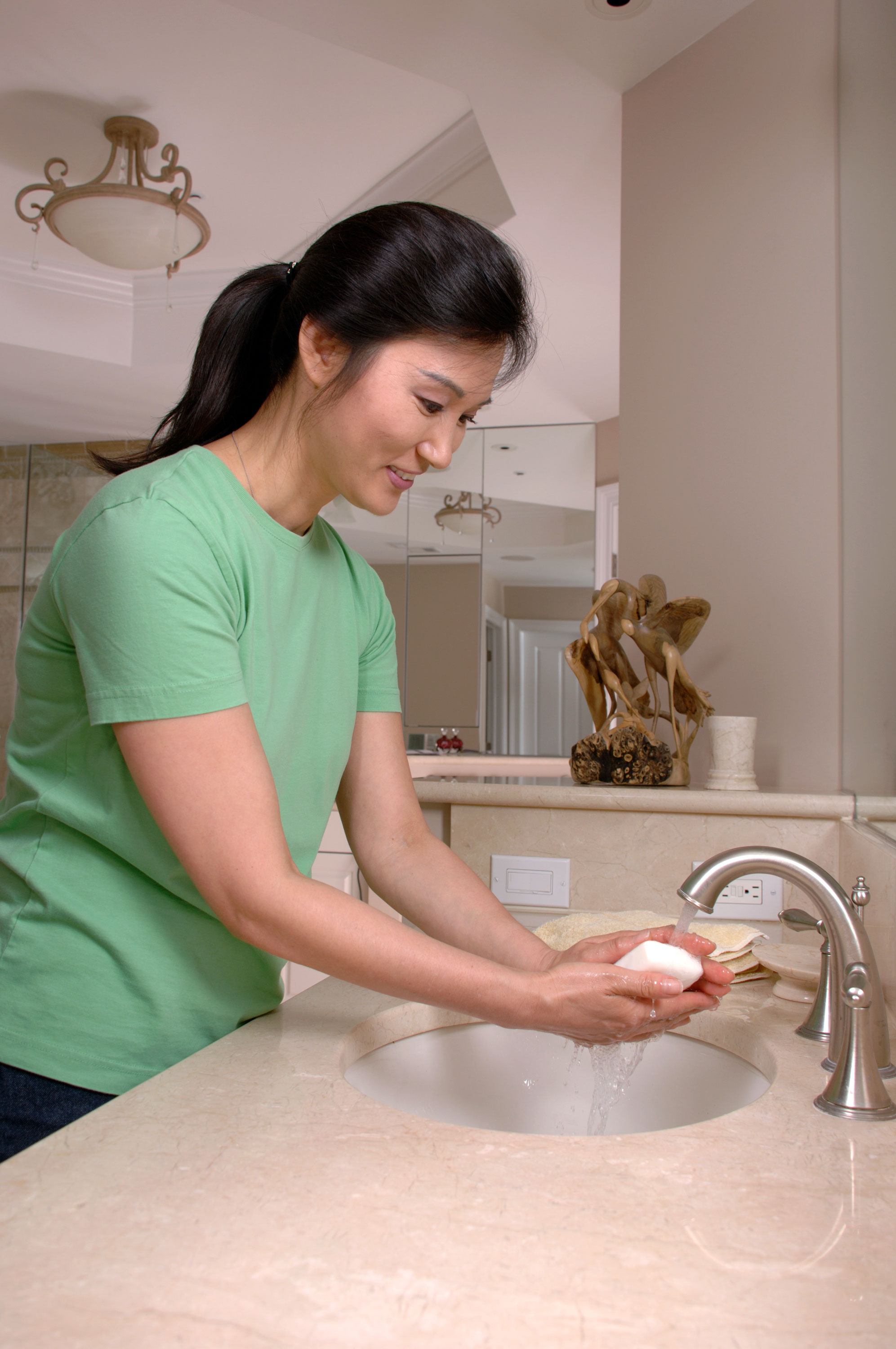 Woman washing hands with soap in the sink.