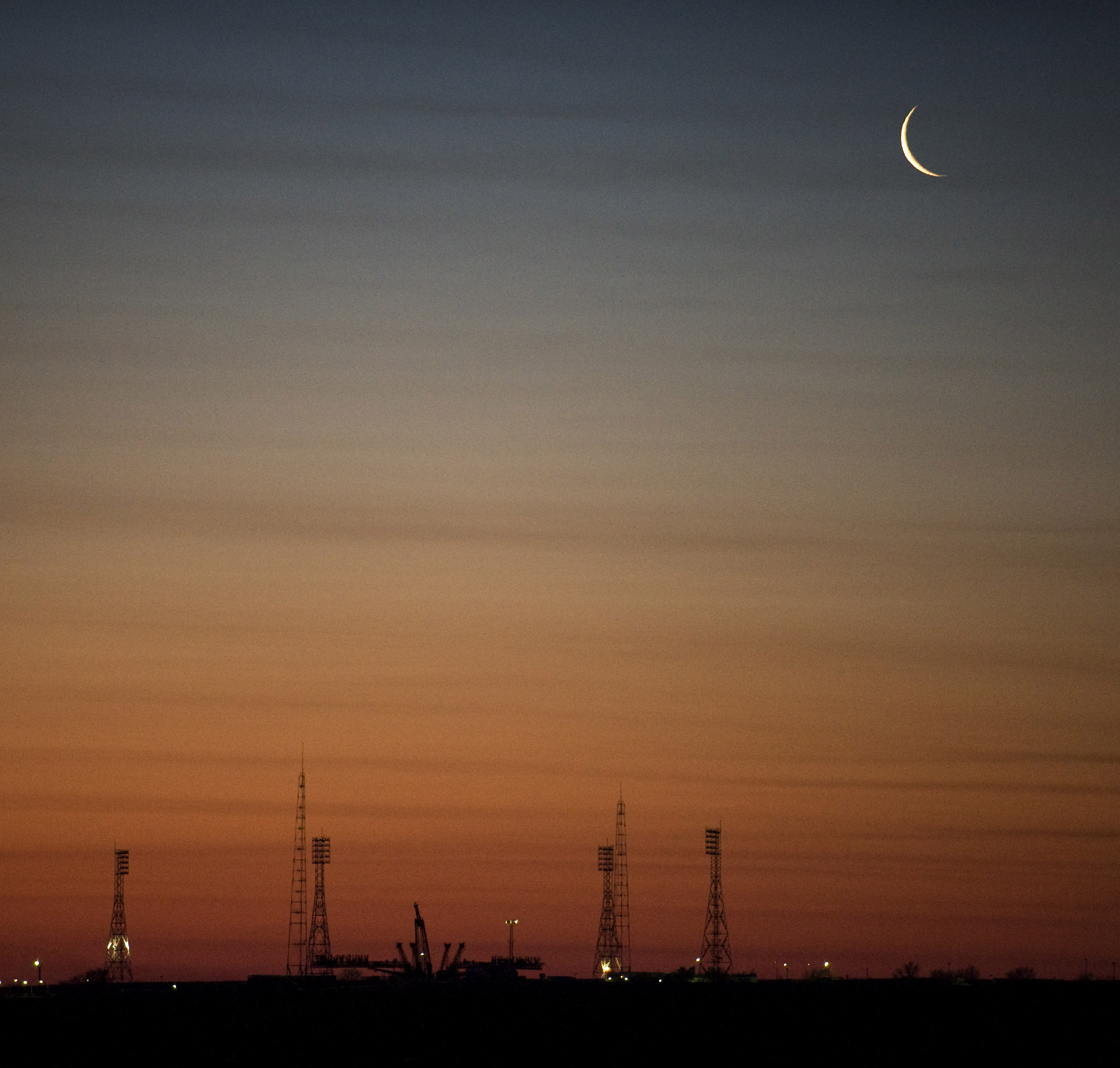 crescent predawn moon over communication towers