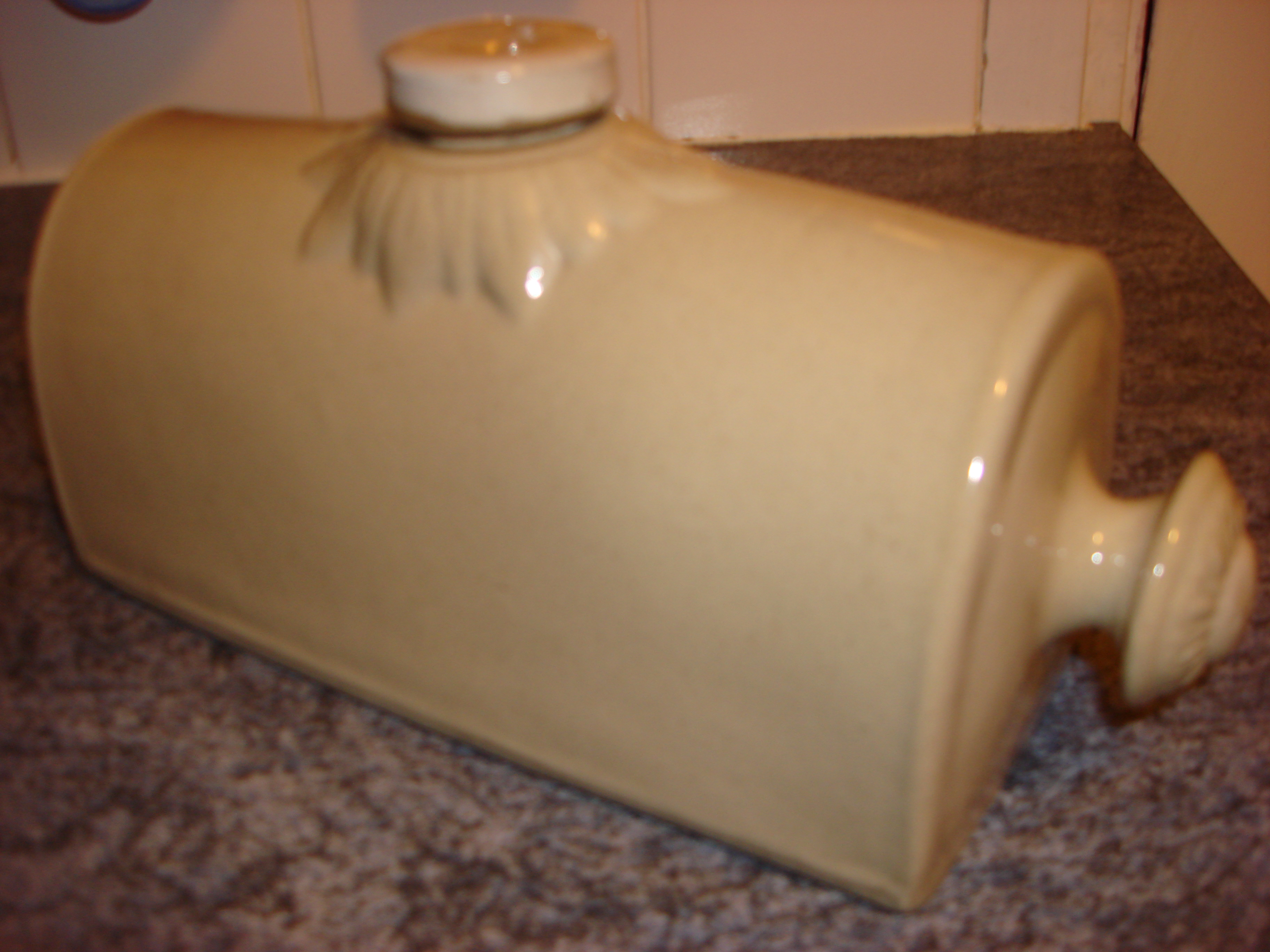 A ceramic hot water bottle with a screw top lid at the top
