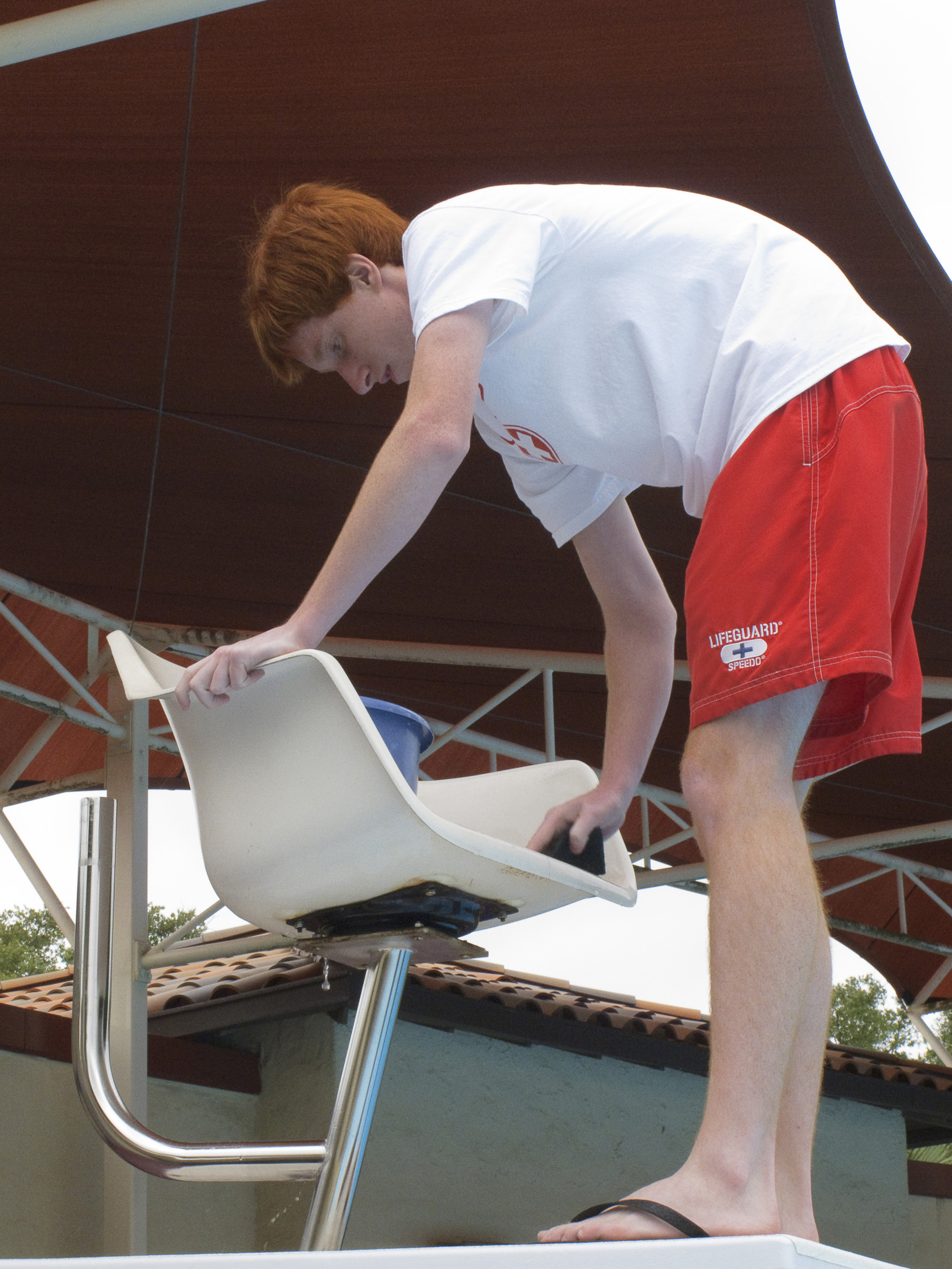 file brian delaney a lifeguard cleans a lifeguard observation chair at a swimming pool during