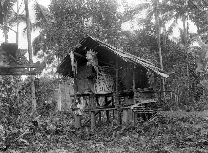 COLLECTIE TROPENMUSEUM Een dorpshoofd in Koetai met kind voor het graf van zijn vader TMnr 10017057