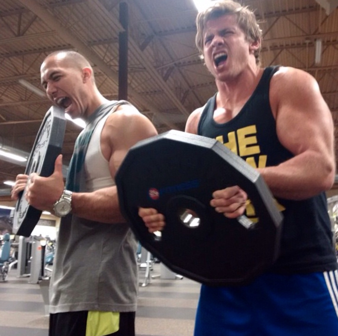 Two men lifting a huge round weight