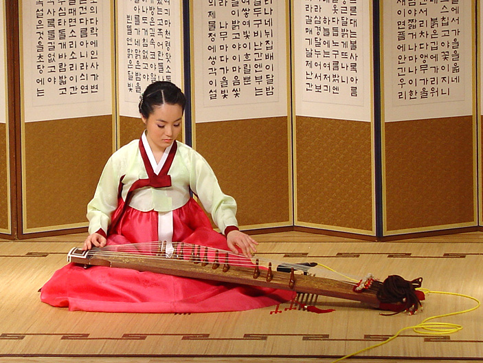 A musician playing a 12-string sanjo gayageum