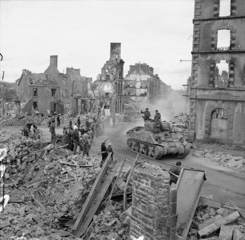 A Sherman drives through the remains of Flers