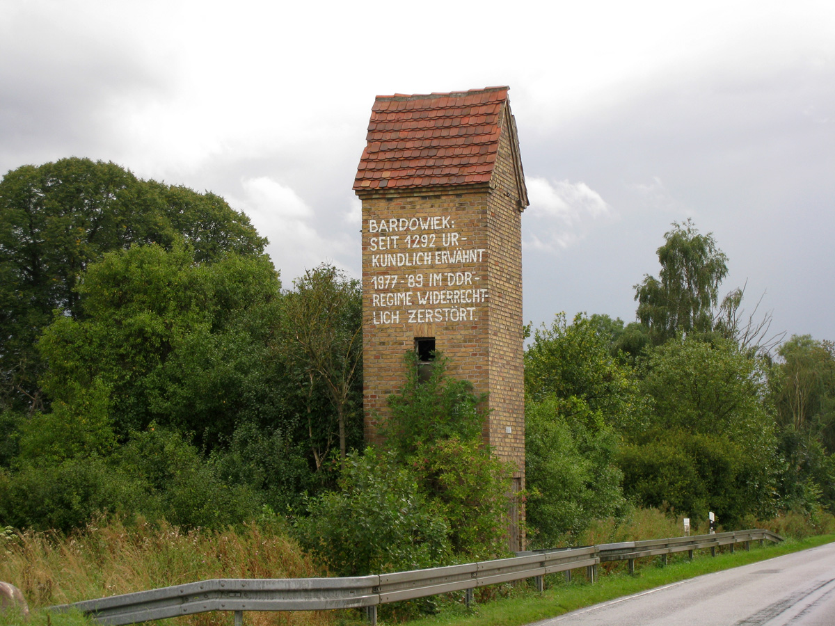 """A small four-storey brick electrical tower with a red tile roof standing next to a road, with trees in the background. There is a wooden door to the right, and a window at first-floor level; the second storey and loft have no windows. The brickwork of the second floor bears a handwritten inscription, daubed with paint: """"BARDOWIEK: SEIT 1292 URKUNDLICH ERWÄHNT 1977–'89 IM """"DDR""""-REGIME WIDERRECHTLICH ZERSTÖRT."""""""