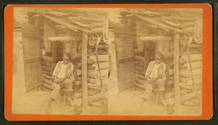 Bob and his fiddle. (Man playing fiddle in front of cabin.), by Havens, O. Pierre, 1838-1912.jpg
