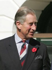 Head and shoulders shot of Prince Charles dressed in a grey suit with a poppy pinned to the left lapelle, blue shirt and red, white and blue striped tie.