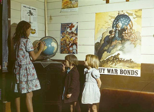 Rural school children in front of World War II homefront posters, 1943