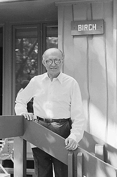 """Fotografia preto-e-brnca de homem muito calvo, de óculos, camisa branca e calça escura, sobre a escada de madeira que leva à porta de uma casa, também de madeira. Na parede atrás, há uma placa em que se lê """"BIRCH"""""""