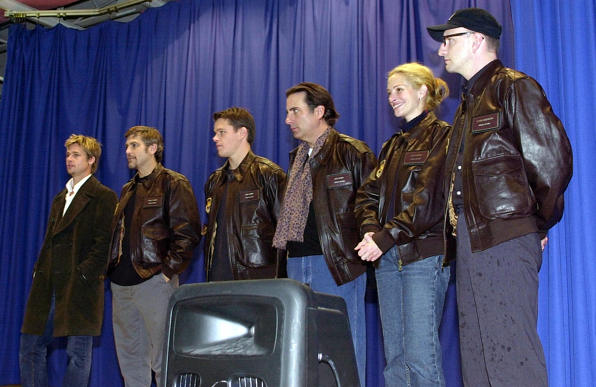 An image of five Caucasian men and one Caucasian woman posing in front of a blue curtain. Four of the men and the woman are wearing leather coats and jeans, while the man on the far left is wearing a trench coat and jeans.