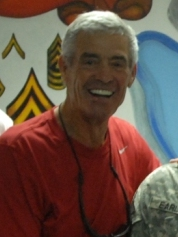 Cropped photograph of Mora in a red t-shirt posing with members of the U.S. military