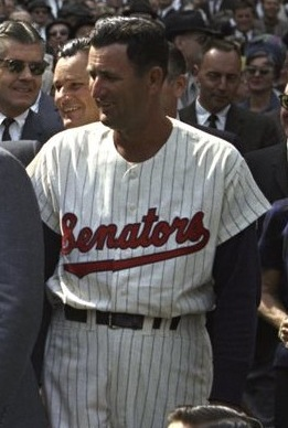 "A man in a white baseball uniform with ""Senators"" on the chest in red"