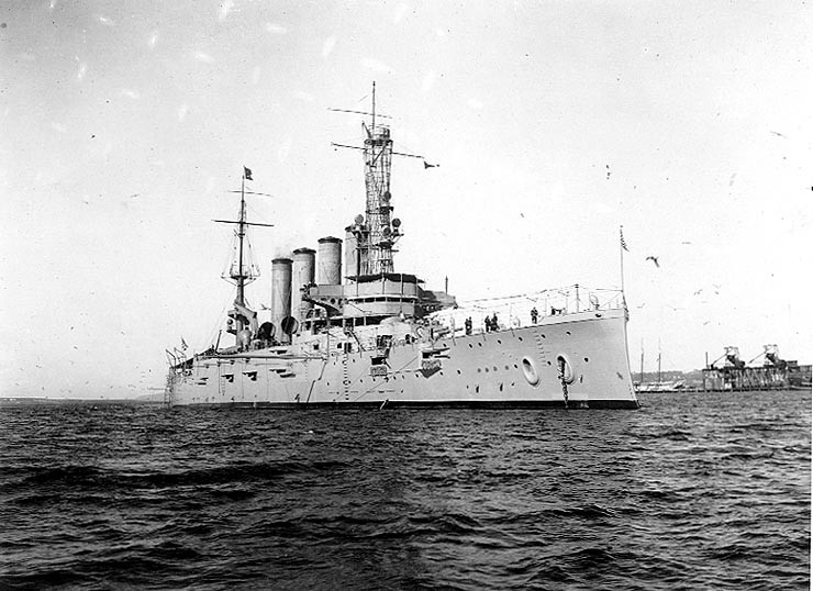 An armored cruiser anchored, with a navy jack flying from the jackstaff.