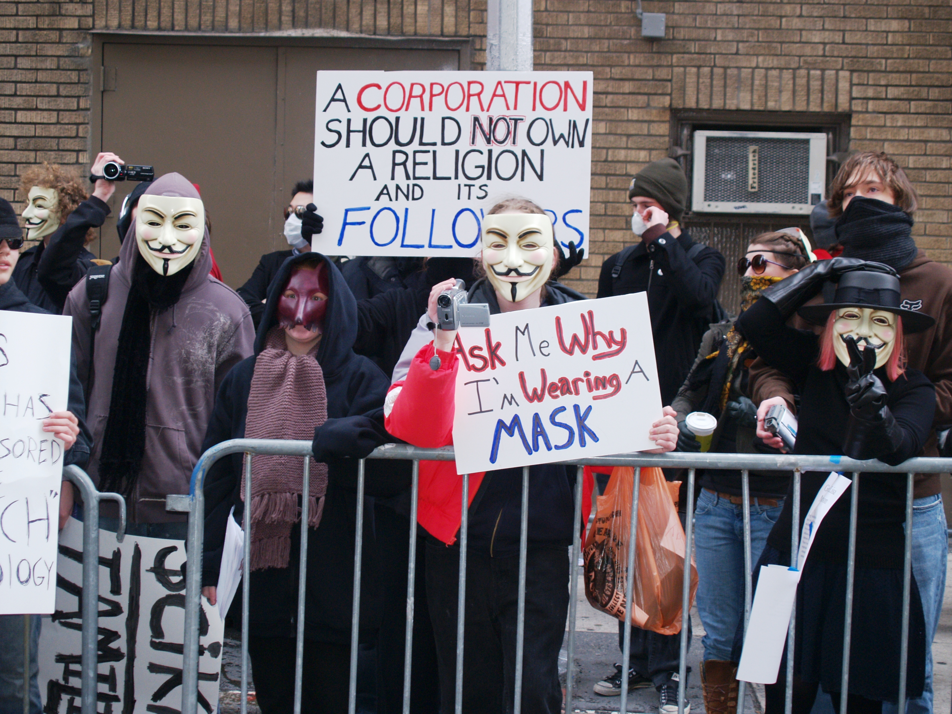 Protest group wearing masks and holding signs