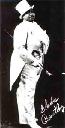 Foto publicitaria de una recia mujer afroamericana vestida con un esmoquin blanco con cola y sombrero de copa, llevando un bastón blanco en la mano y su firma en la esquina inferior derecha