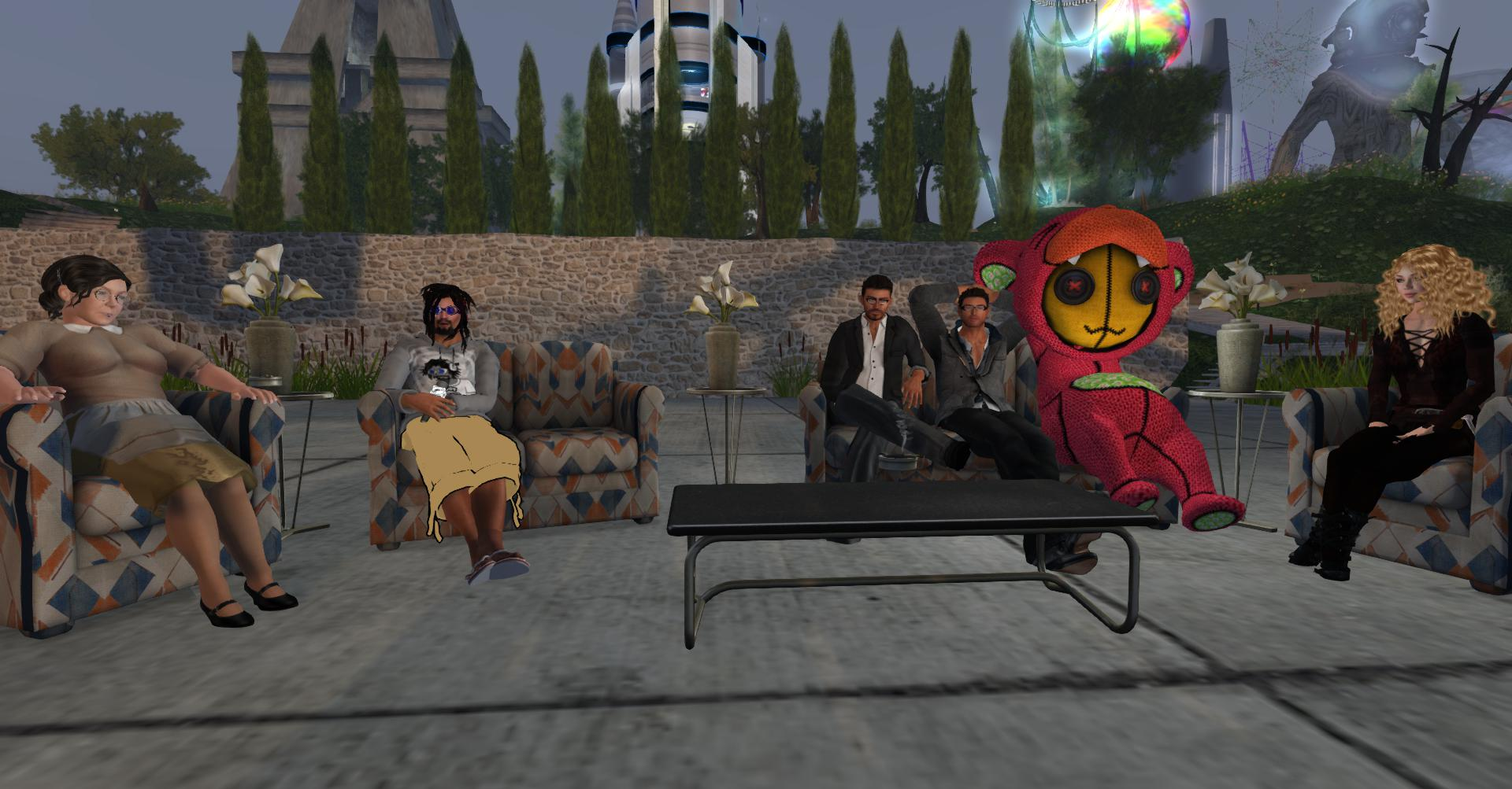 Photo showing six people from Second Life sitting around a table, one dressed in a costume. They look relaxed.