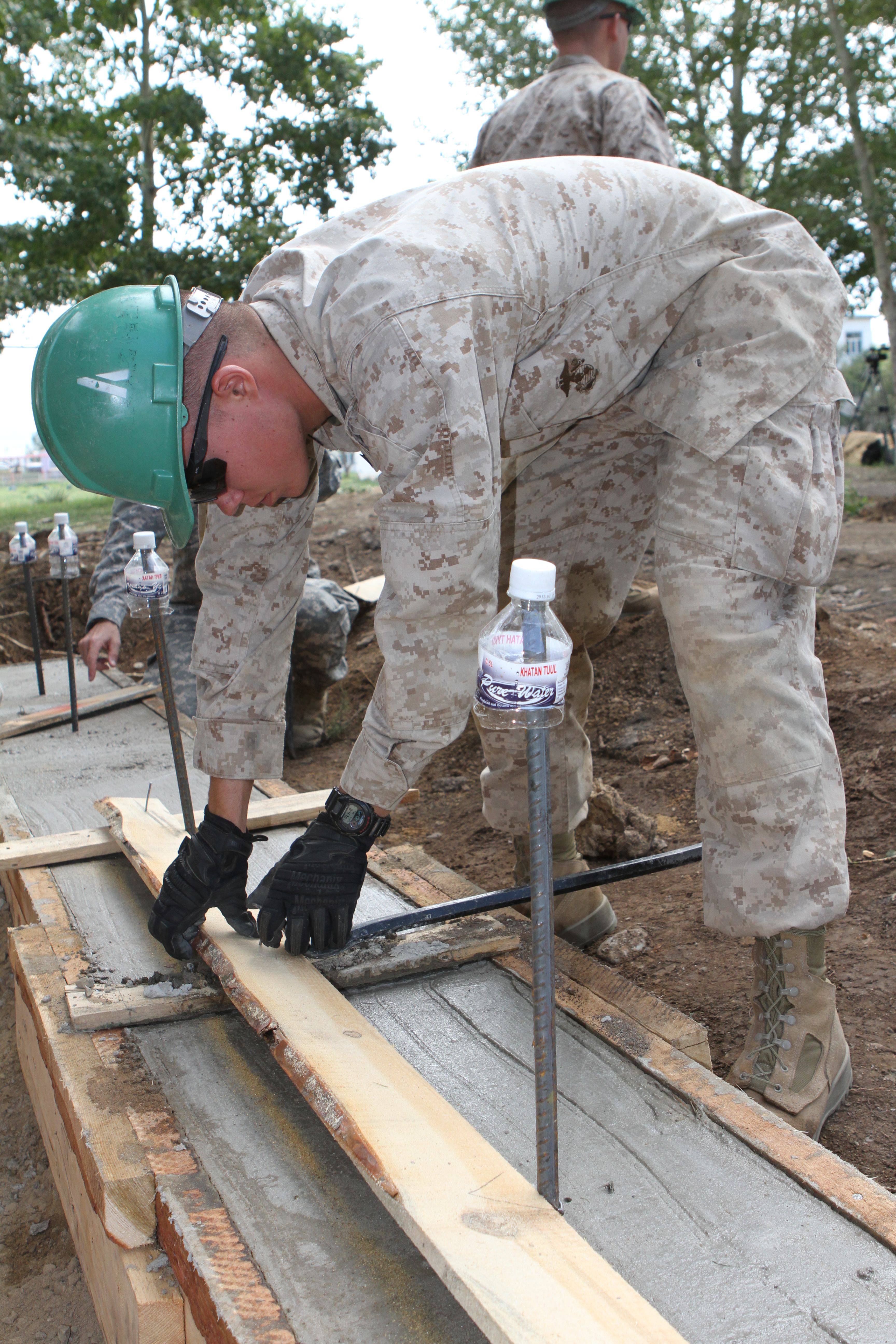 III Marine Expeditionary Force, removes frames from new concrete during renovation work on 130725-M-DR618-019.jpg English: U.S. Marine Corps Lance Cpl.