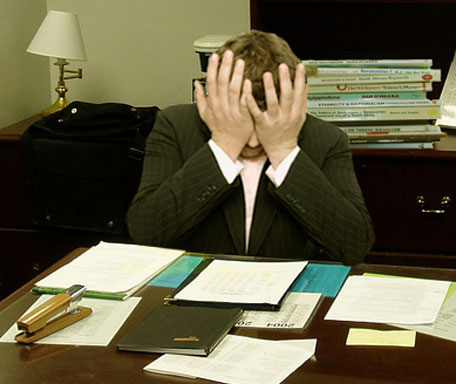 Frustrated man at a desk (cropped)
