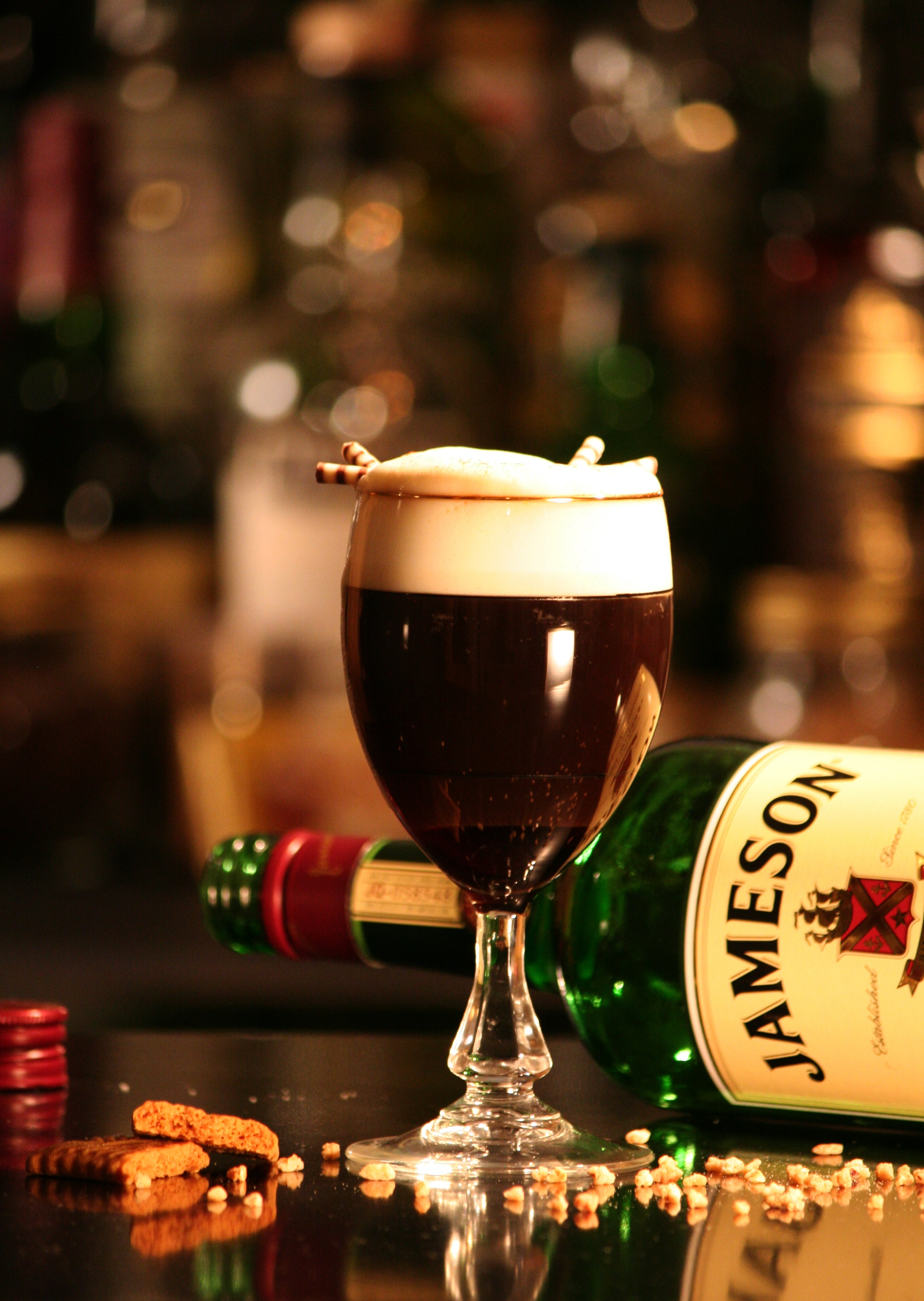 Cup of Irish coffee topped with cream, and a bottle of Jameson whiskey behind it