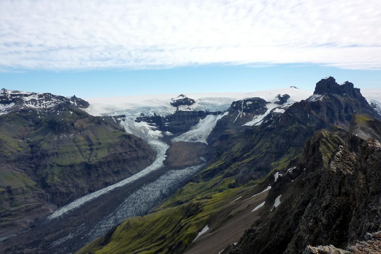 Blick von den Kristínartindar-Gipfeln auf den Morsárfoss in den Felsen in der Bildmitte; auf den Felsen liegt die Eiskappe des Vatnajökull, unterhalb von ihnen beginnt der Morsárjökull.