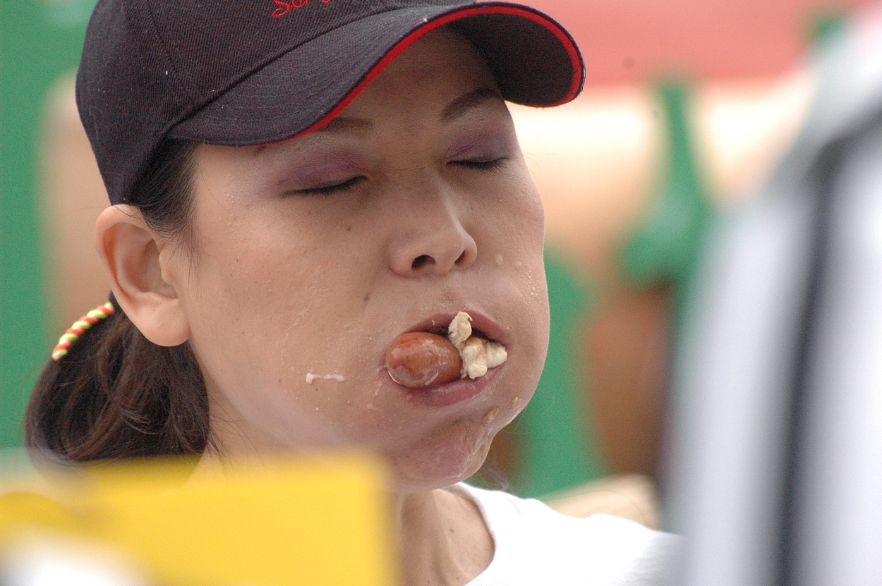 Girl with Mouth Full of Hot Dogs