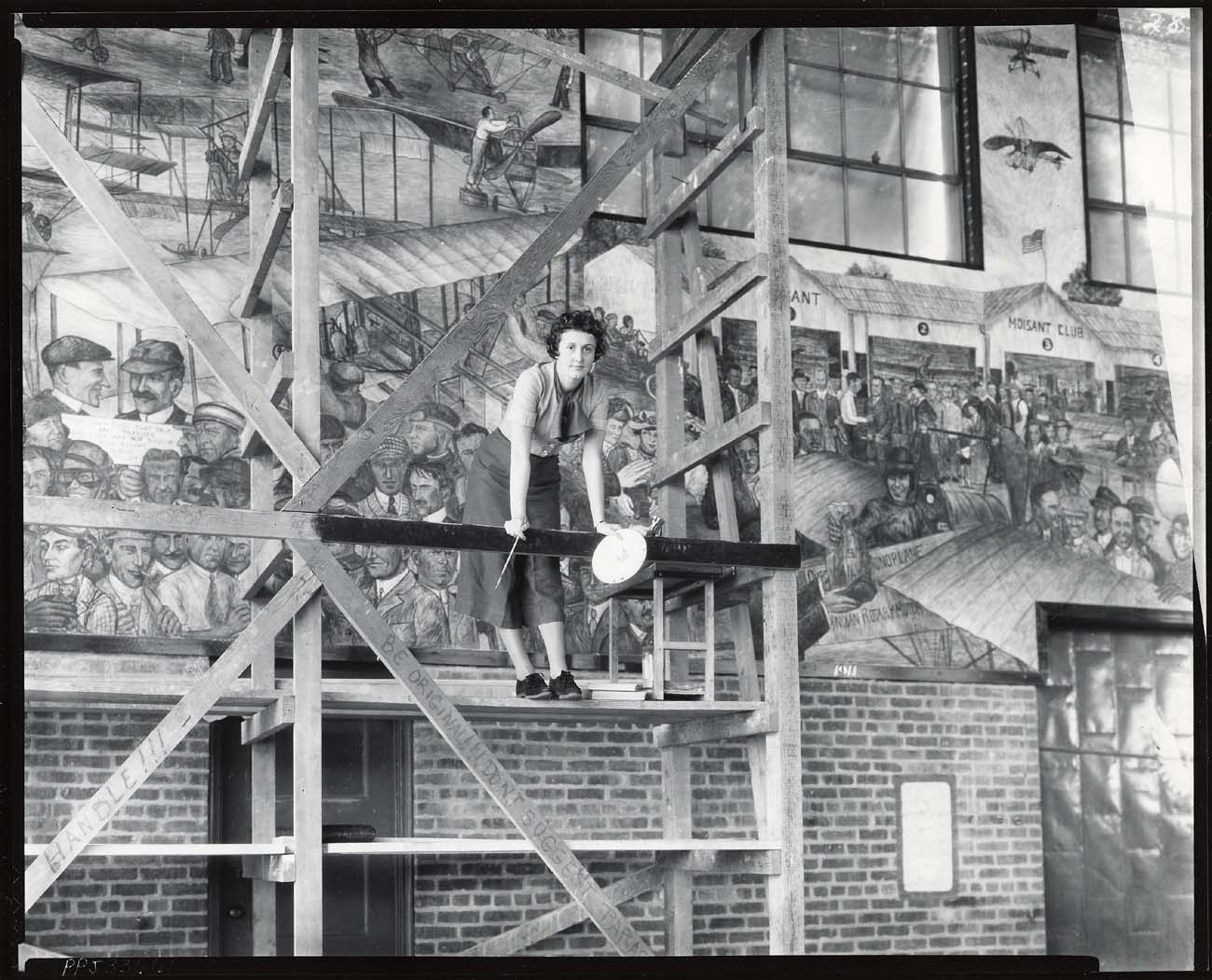 File aline h rhonie american painter 1909 1963 at work on aviation mural at roosevelt field for Roosevelt field garden city ny