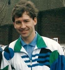 Photographie en couleurs. Portrait de Bryan Robson en survêtement sportif bleu, blanc, vert et noir, souriant et les cheveux désordonnés par le vent.