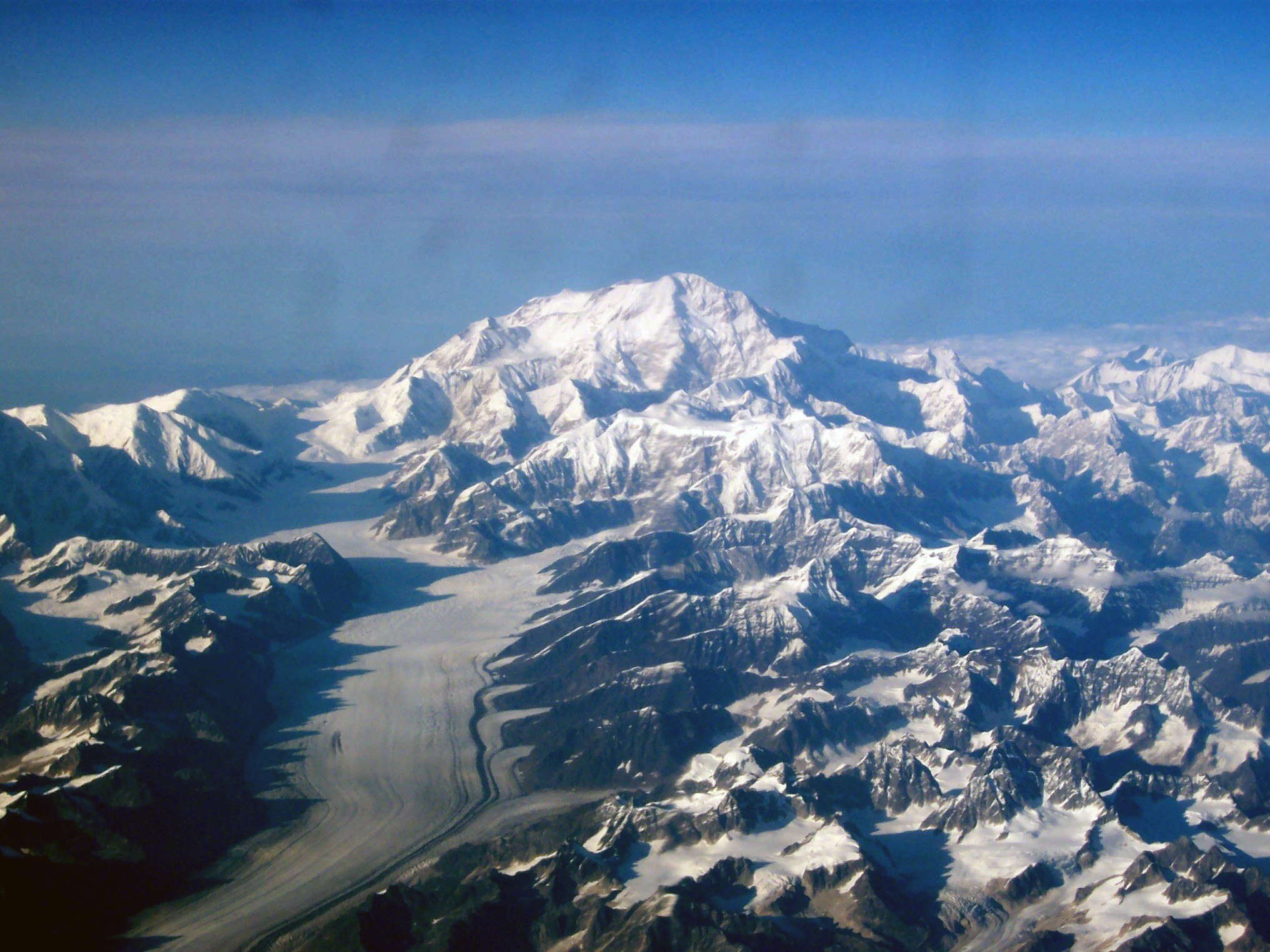 In An Aerial Image A Mountain Is Surrounded By Many Smaller Mountains And A Glacier