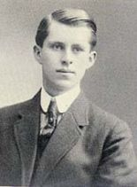 Waist high portrait of man in his teens wearing a suit, leaning to his left so his right shoulder is cut off