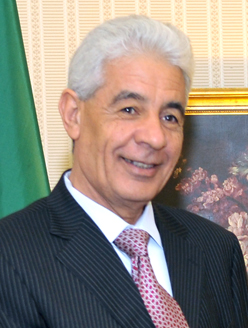 head shot of smiling, white-haired man in western business attire