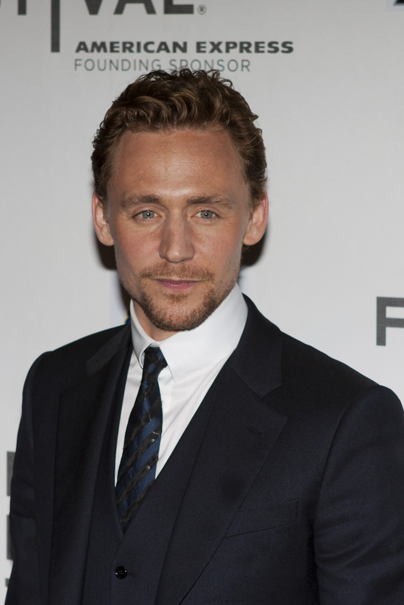 Tom Hiddlestone at the Avengers premiere, wearing a black suit, waistcoat and tie, and a white shirt.
