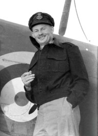 Informal portrait of grinning man in peaked cap and military uniform leaning against an aircraft fuselage