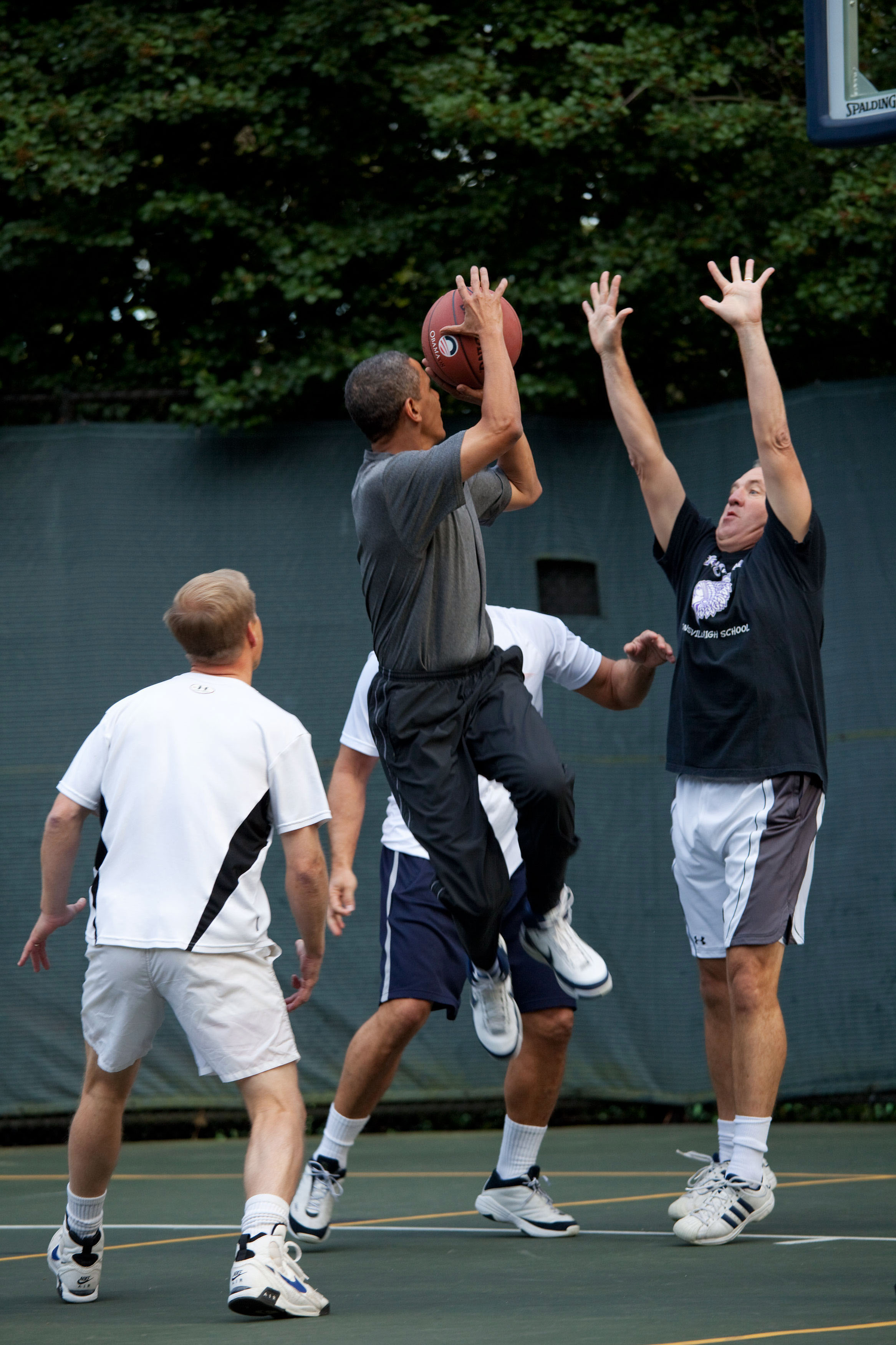 Obama about to take a shot while three other players look at him. One of those players is holding is arms up in an attempt to block Obama.
