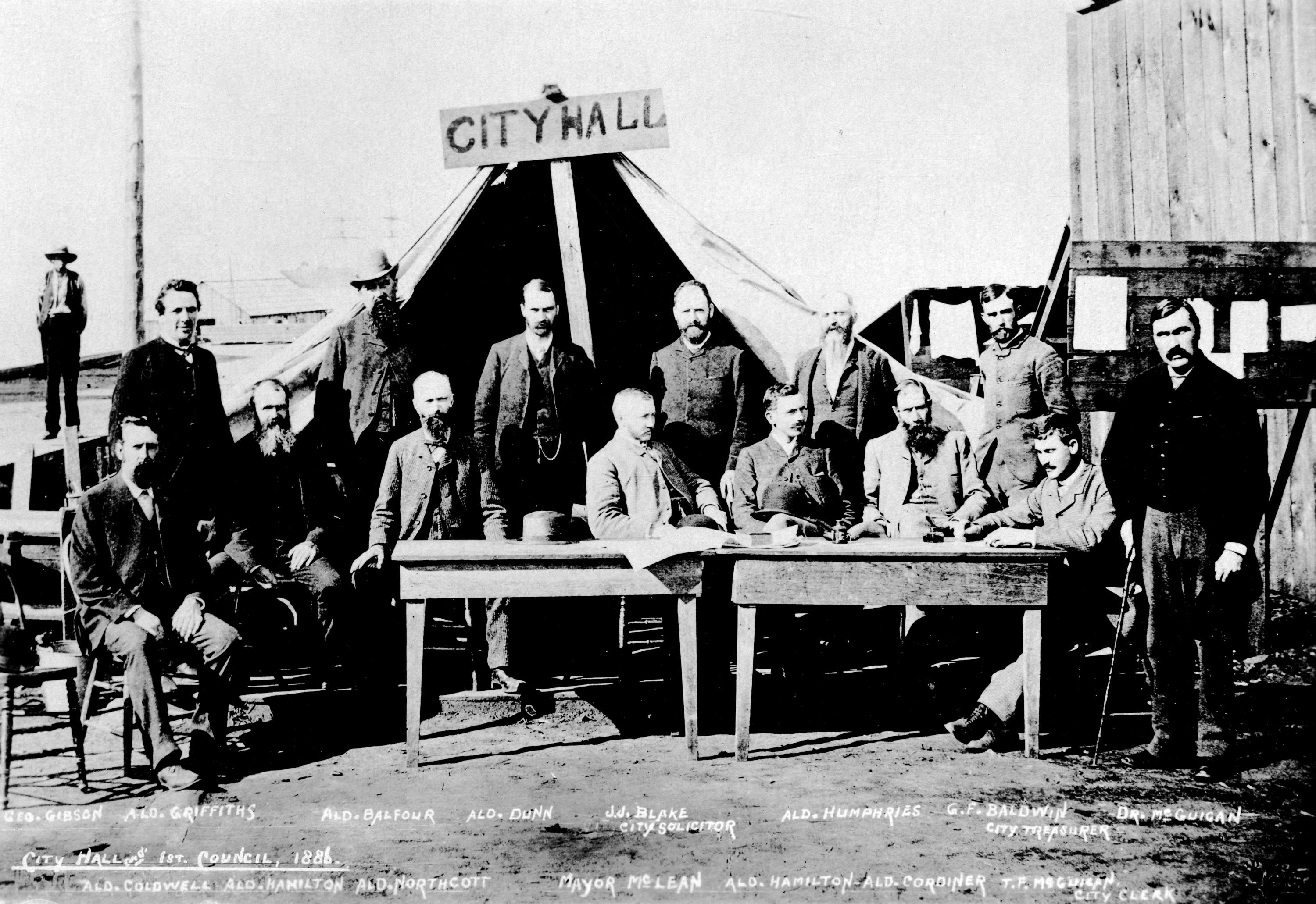 "Men standing and sitting around two tables, facing the camera. A large tent behind them has a wooden sign that reads ""City Hall"""