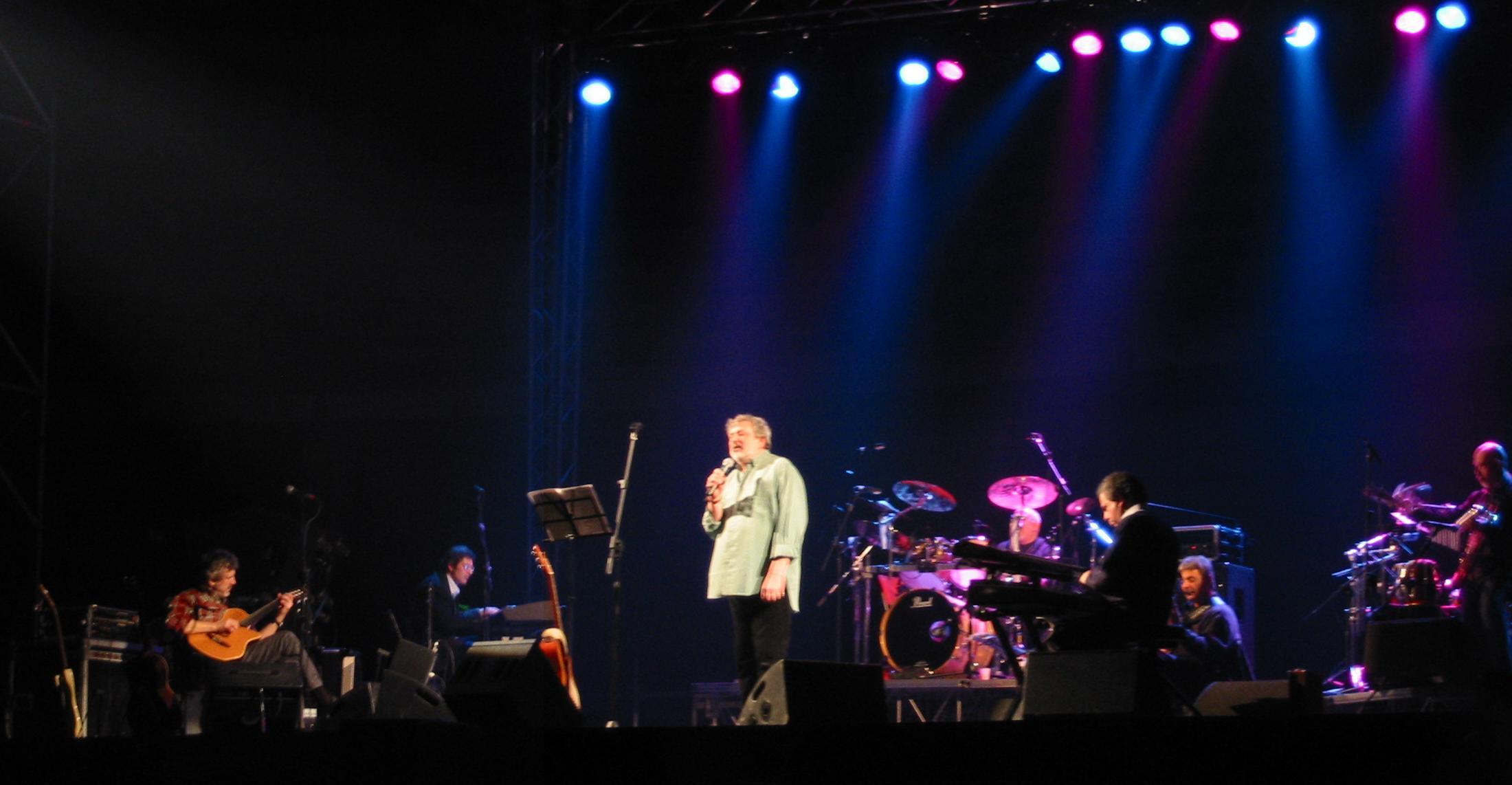 """Guccini en concierto en el Palaghiaccio de Marino, marzo 2003.De izquierda a derecha: """"Flaco"""" Biondini (guitarra), Roberto Manuzzi (teclado), Francesco Guccini, los ex miembros de The Pleasure Machine (Ellade Bandini (batería), Vence Tempera (teclados) y Ares Tavolazzi (bajo)), y Antonio Marangolo (saxo)."""