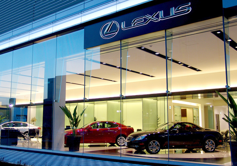 alt=Car showroom with a coupe, two sedans, glass windows, plus large sign reading