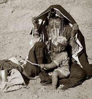 אישה בדואית יושבת עם בנה במדבר