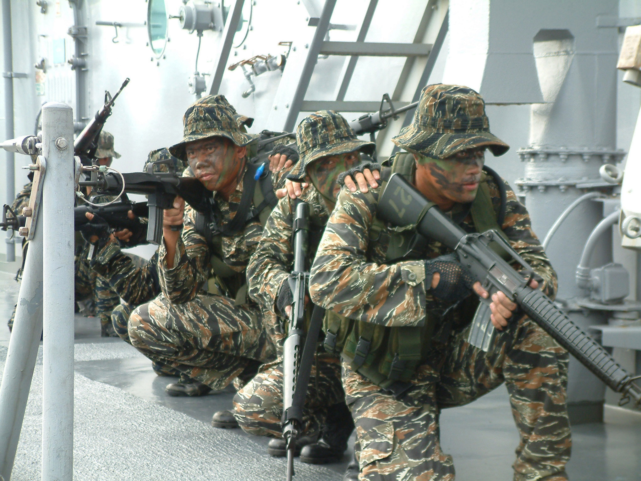 Pintar réplicas US_Navy_040730-N-7720S-045_Members_assigned_to_the_Philippine_Naval_Special_Warfare_Group_(SWAG)_Nine_One_crouch_low_and_move_together_on_the_deck_aboard_the_amphibious_dock_landing_ship_USS_Fort_McHenry_(LSD_43)
