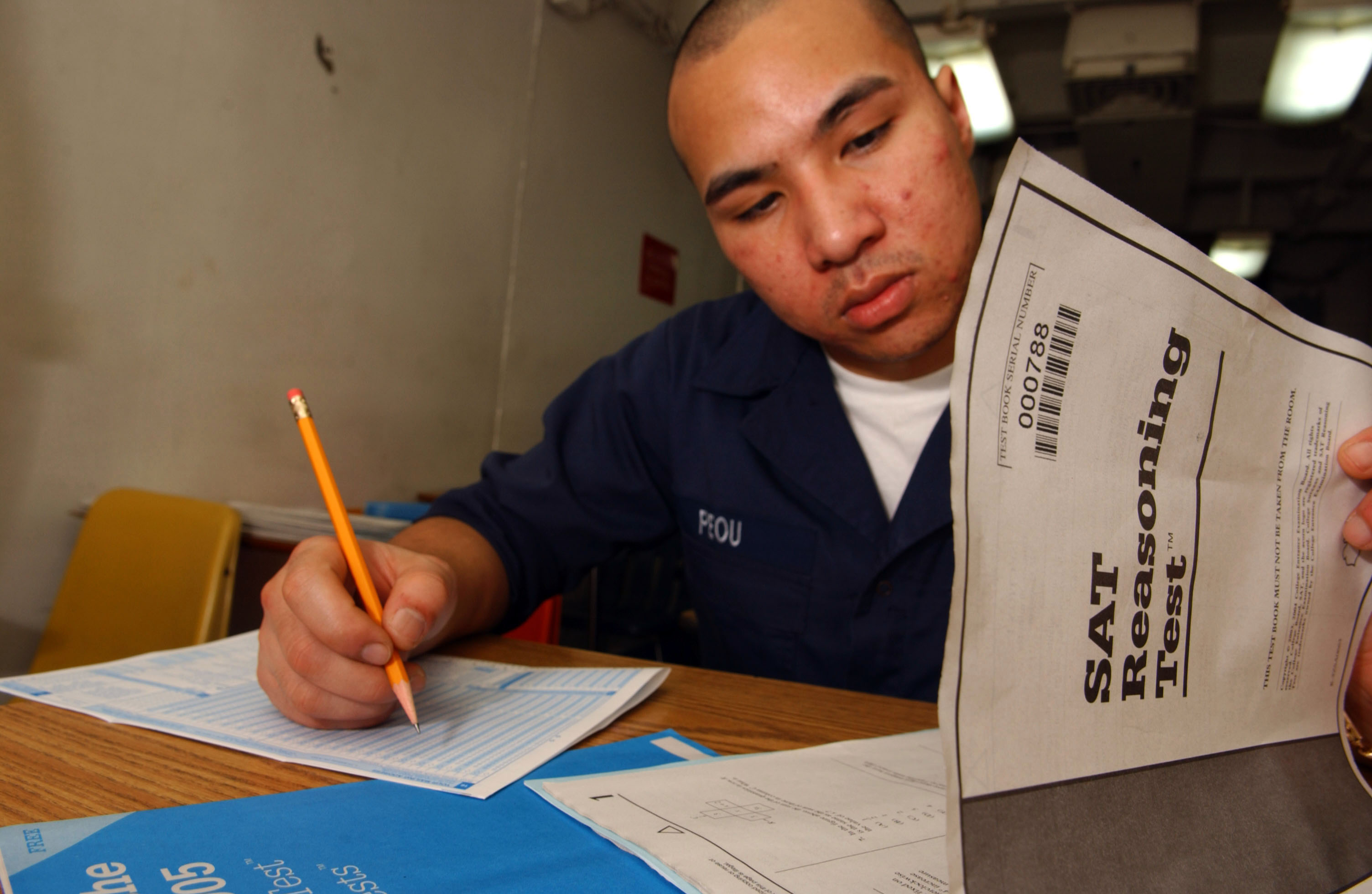 US Navy 050223 N 5821P 054 Seaman Chanthorn Peou of San Diego%2C Calif.%2C takes his Scholastic Aptitude Test %28SAT%29 aboard the conventionally powered aircraft carrier USS Kitty Hawk %28CV 63%29 Calculator Policies on the ACT and SAT