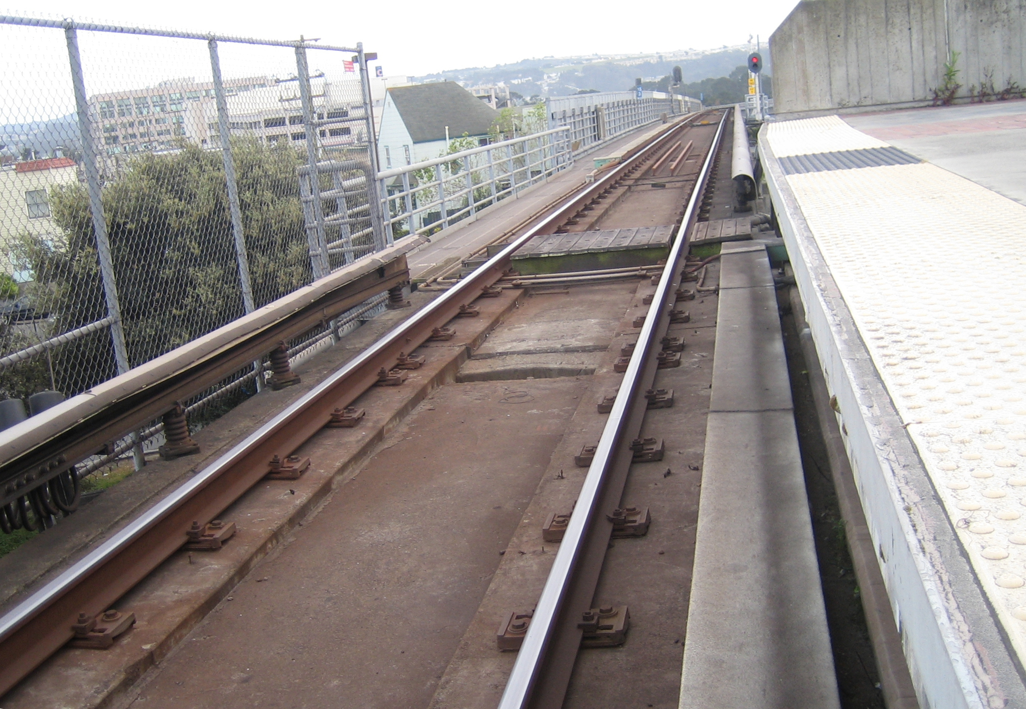 The location of the BART's third rail changes relative to the train when it enters the station and meets the walkway crossing the trackway. On the left side of the trackway in the distance is the emergency walkway for the aerial trackway leading into the station the third rail is positioned opposite this walkway.
