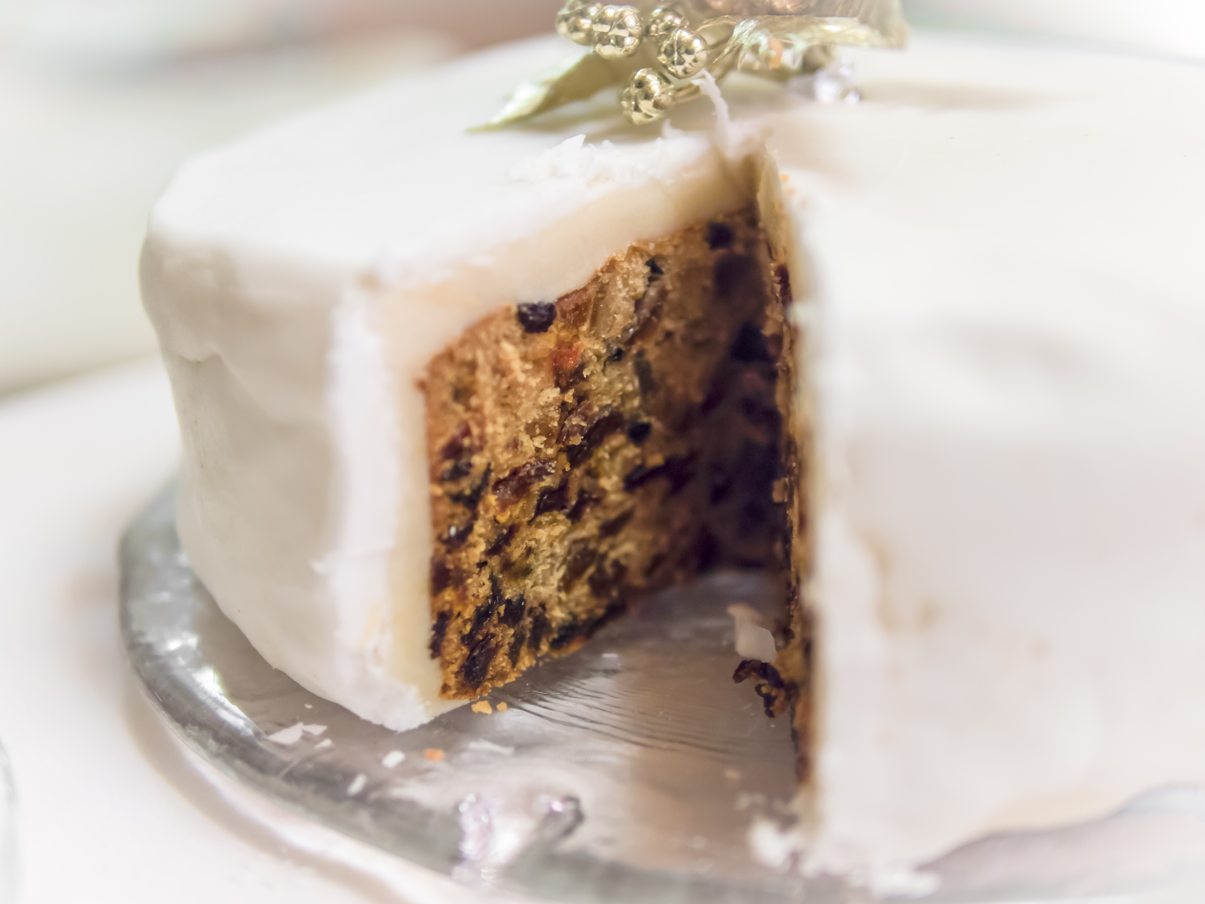 A British Christmas cake with icing and marzipan.  One slice is removed to reveal the rich fruit cake inside