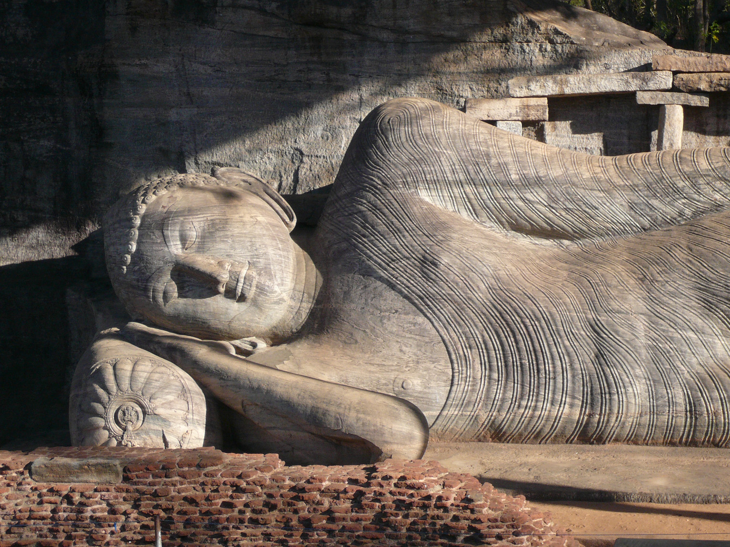 Reclining Buddha in Gal Vihara, Polonnaruwa. The picture is taken at a time when the shadow of the roof has not yet touched the image. Zoom in from quite a distance.